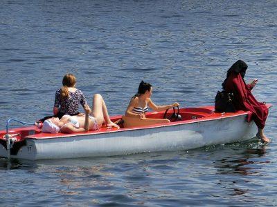 women on a boat, contrasting attire: bikins, niqab